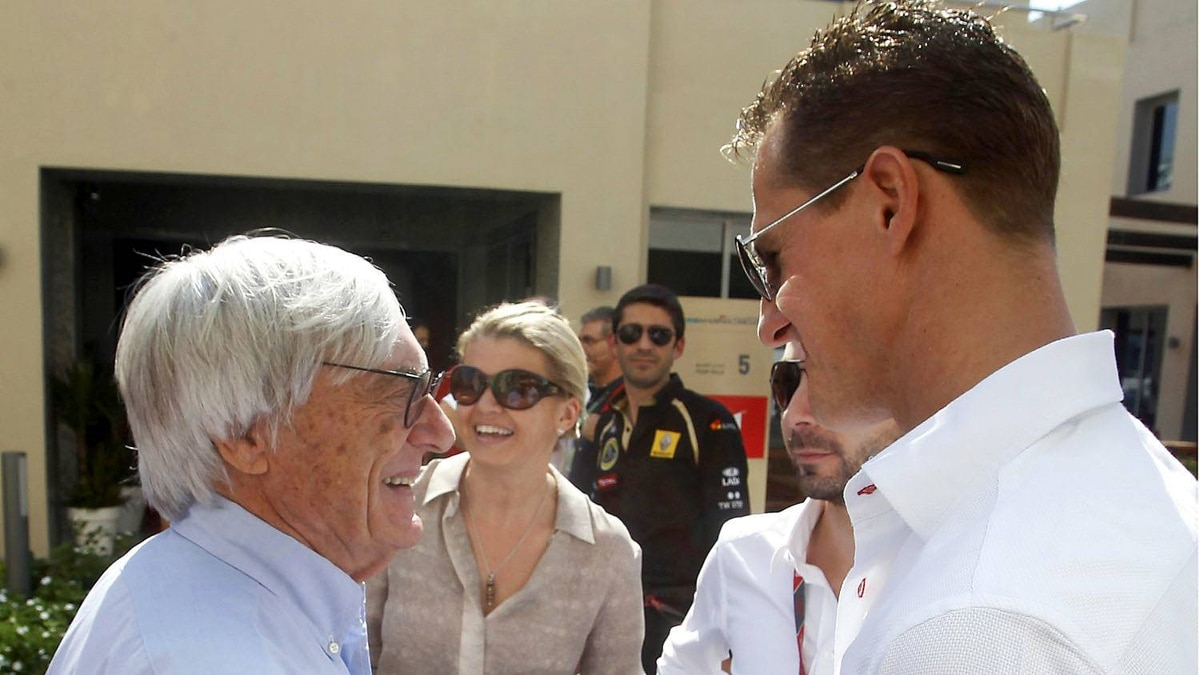 Bernie Ecclestone, president and CEO of Formula One Management, left, shakes hands with Mercedes driver Michael Schumacher of Germany in the paddock ahead the Emirates Formula One Grand Prix at the Yas Marina racetrack in Abu Dhabi, United Arab Emirates, Sunday, Nov. 13, 2011. The head of Formula One expressed doubts on Saturday whether the 2012 United States Grand Prix in Austin, Texas, will go ahead as scheduled.