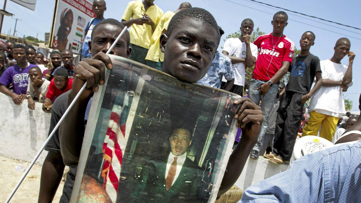 A man holds an old portrait of Charles Taylor at an area where people gathered in the Sinkor neighborhood of Monrovia on April 26, 2012.