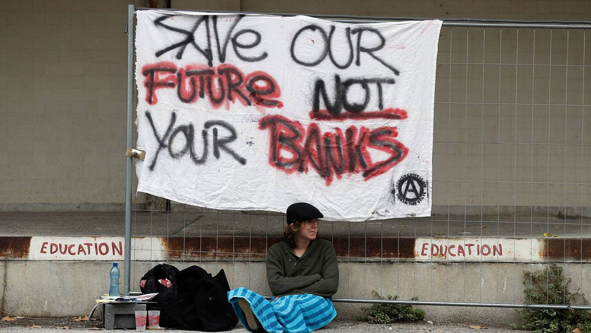A lone demonstrator sits and waits underneath a banner at Nice's old abbatoir, the meeting place for anti-G20 protesters, Nov. 2, 2011 in Nice, France. Christopher Furlong/Getty Images