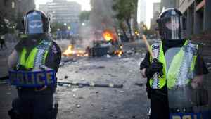 Riot police stand guard at Hamilton Street and Georgia Street after the Bruins won the Stanley Cup and cars were set ablaze in Vancouver on June 15, 2011.