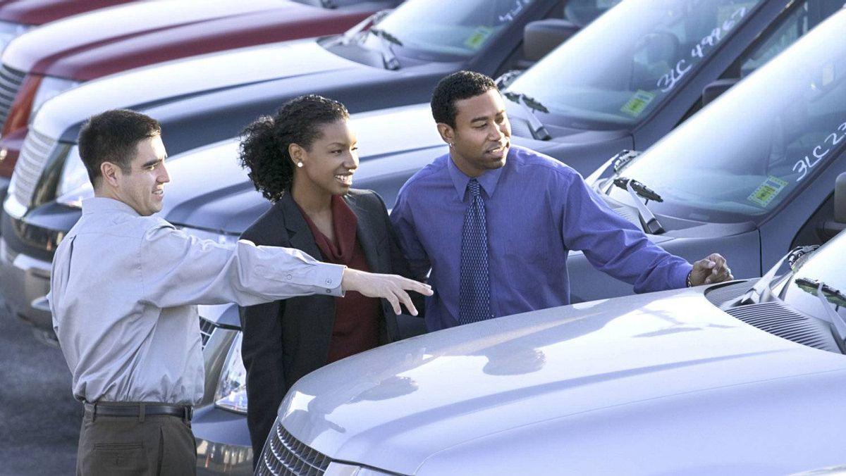 Salesman and couple car shopping.