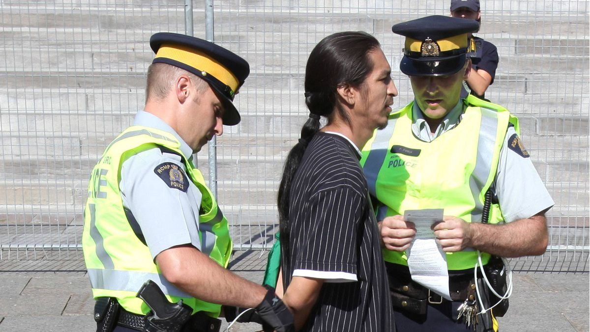 A demonstrator is arrested after crossing a police barricade during a protest against the Keystone XL pipeline on Parliament Hill in Ottawa September 26, 2011.