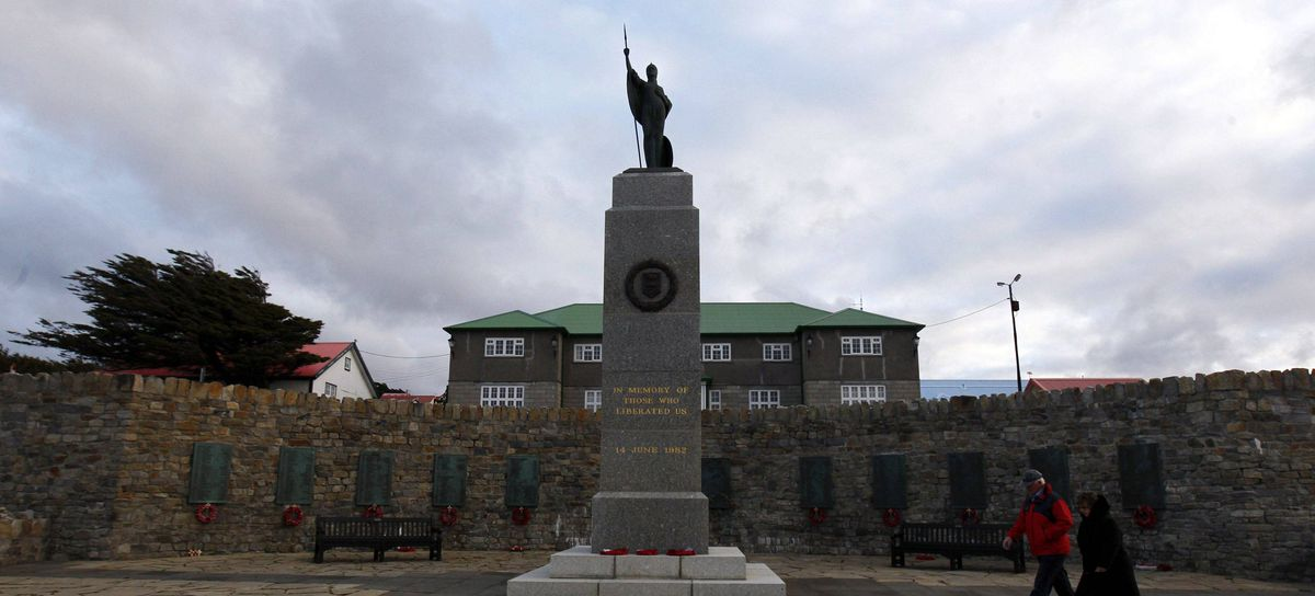 Pedestrians walk by the Liberation Monument in Port Stanley March 10, 2012.