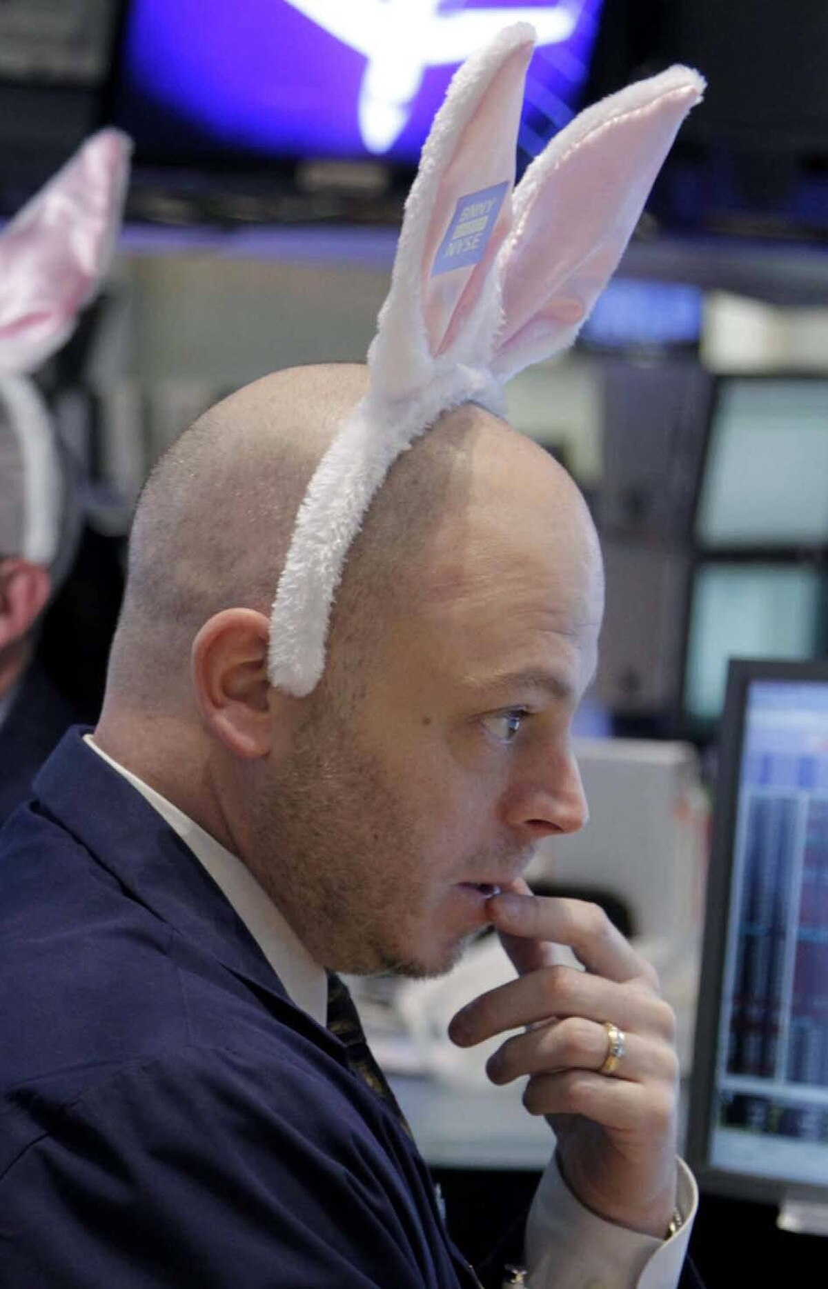 Meanwhile, on Wall Street, a trader wears pink bunny ears in an effort to humanize himself in your eyes as he ponders a way to sell the debt you owe on your overpriced house back to you as an investment so that, when the day comes that you lose your house because you can't make the mortgage payments, you also lose all your savings! Go Wall Street!