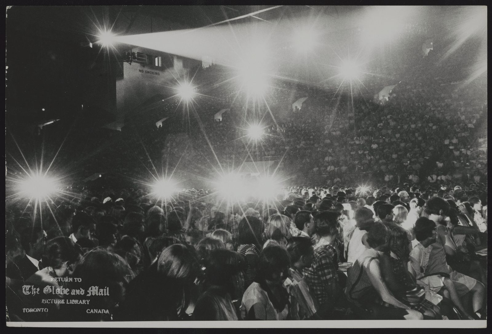 The notes transcribed from the back of this photograph are as follows: BEATLES As soon as the famed quartet appeared before the audience, thousands of flashbulbs began to pop.