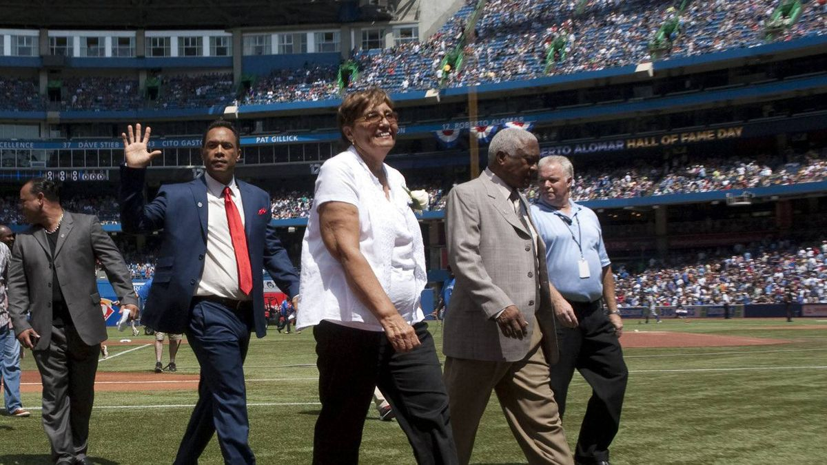 Roberto Alomar waves to the crowd as he walks accross the pitch with his father Roberto Snr (right) and mother Maria (center right) as his shirt is retired ahead of Texas Rangers Toronto Blue Jays MLB baseball action in Toronto on Sunday July 31, 2011. THE CANADIAN PRESS/Chris Young