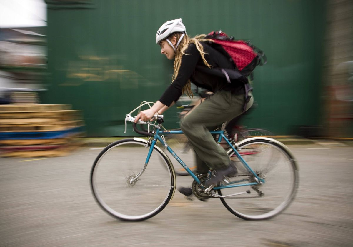 Robin Pickell, 23, a 'freegan', rides her bike to different dumpsters to find edible food in an alley behind Commercial Drive. Freegans aim to spend little or no money purchasing food and other goods, not through financial need but to try to address issues of over-consumption and excess.