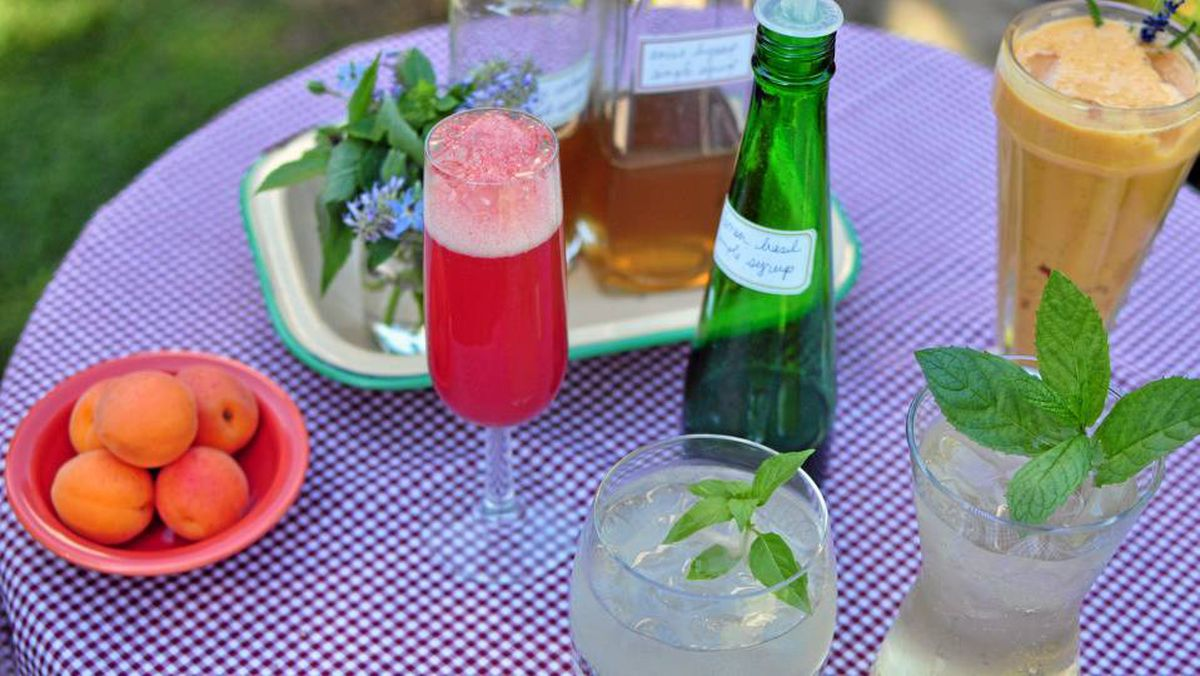 Gayla Trail's fondness for growing herbs has resulted in a repertoire of unusual drinks recipes, including (clockwise from left) watermelon/mint prosecco, lavender and apricot smoothies, lemon basil spritzers and lemon basil gimlets. A key ingredient in the last two is homemade lemon basil simple syrup (middle).