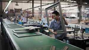 A worker operates on a picture and mirror frame assembly line at a factory in Zibo, Shandong Province May 28, 2012.
