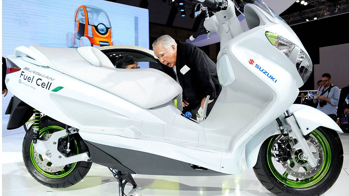 Osamu Suzuki, chairman of Suzuki Motor, inspects the company's Burgman fuel cell motorcycle.