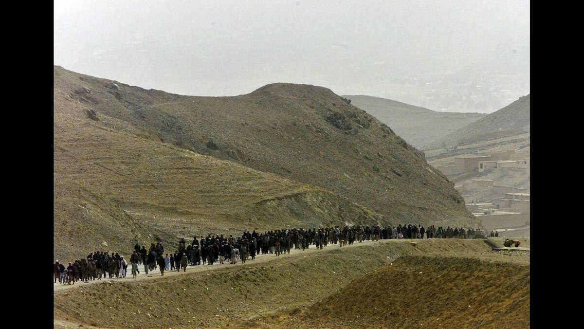 Residents of Kabul make their way to greet Northern Alliance fighters arriving in the outskirts of the Afghan capital Kabul, November 13, 2001.