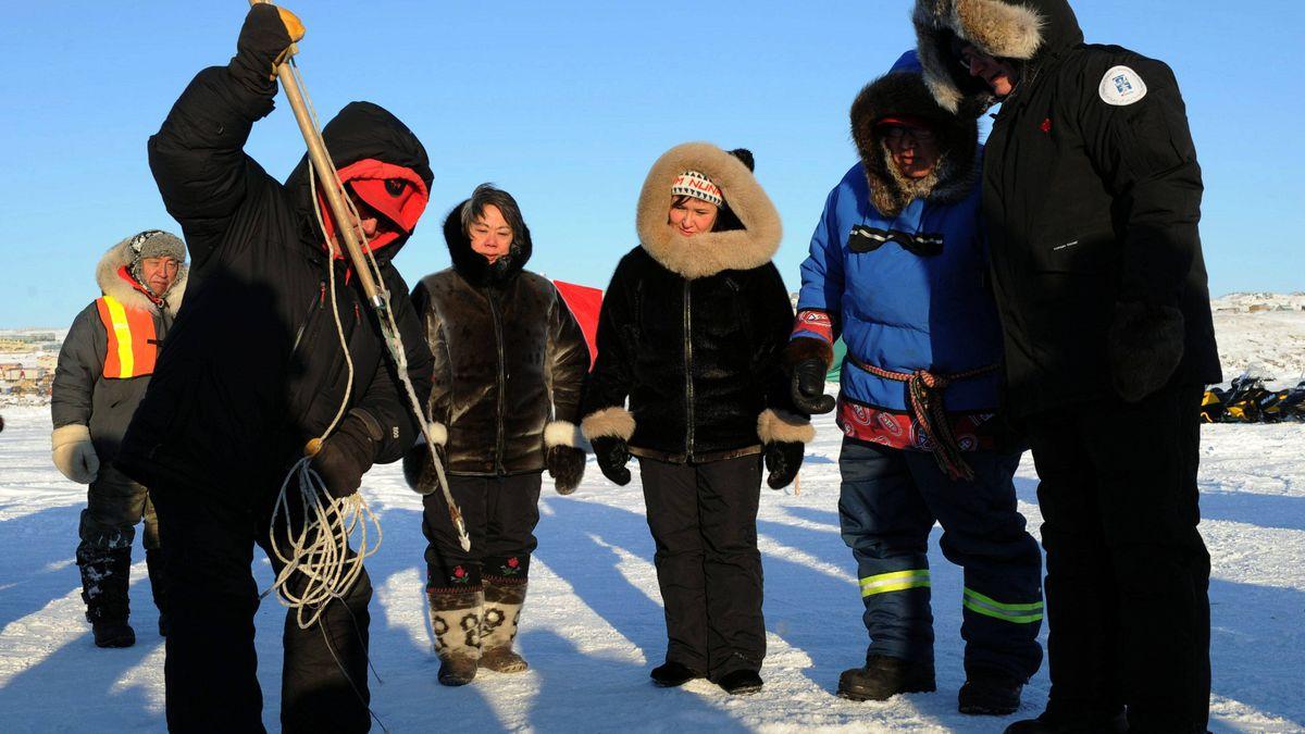 From right: Prime Minister Stephen Harper Canadian Ranger Dinos Tikivik, Health Minister Leona Aglukkaq and Nunavut Premier Eva Aariak watch as Moses Atagooyuk gives a seal hunting demonstration in Iqaluit, Nunavut, on Feb. 23, 2012.