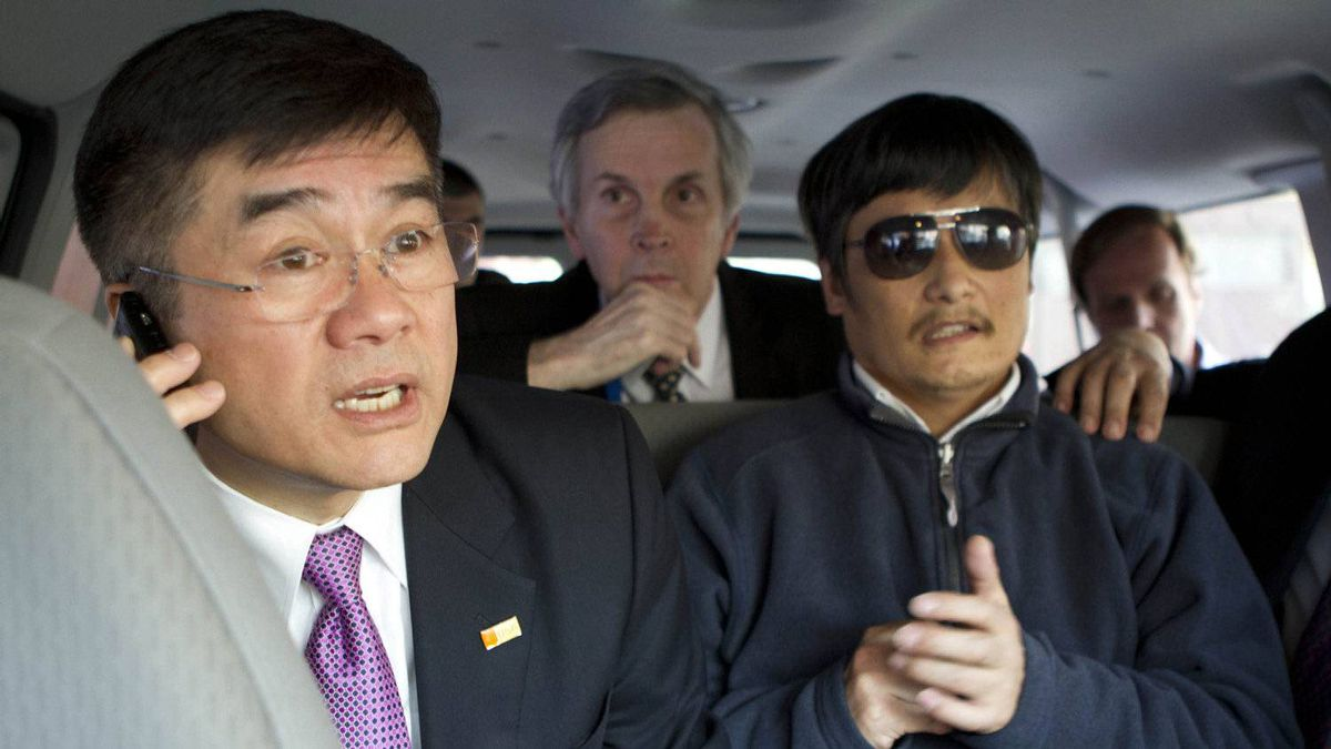In this photo released by the US Embassy Beijing Press Office, U.S. ambassador to China, Gary Locke, left, makes a phone call as he accompanies blind lawyer Chen Guangcheng, right, in a car en route from the U.S. Embassy to a hospital in Beijing, Wednesday, May 2, 2012. At center is language attache James Brown.