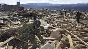 Rescue workers look for survivors while going through debris in Rikuzentakada People in Iwate Prefecture (State), Saturday morning, March 12, 2011, a day after a strong earthquake-triggered devastating tsunami hit the northern Japan.