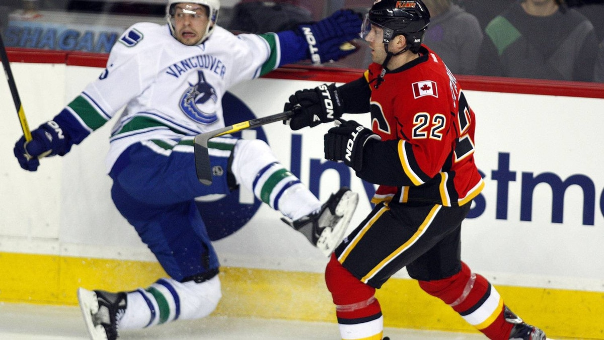 Vancouver Canucks' Marc-Andre Gragnani, left, crashes to the ice after a check by Calgary Flames' Lee Stempniak during first period NHL hockey action in Calgary, Alta., Thursday, April 5, 2012. Stempniak is completing a 2-year contract worth 3.8-million dollars.