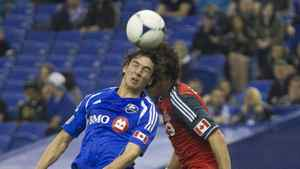 Montreal Impact's Zarek Valentin (19) fights for the ball with Toronto FC's Logan Emory (R) during the first half of their MLS soccer match in Montreal, Quebec April 7, 2012.
