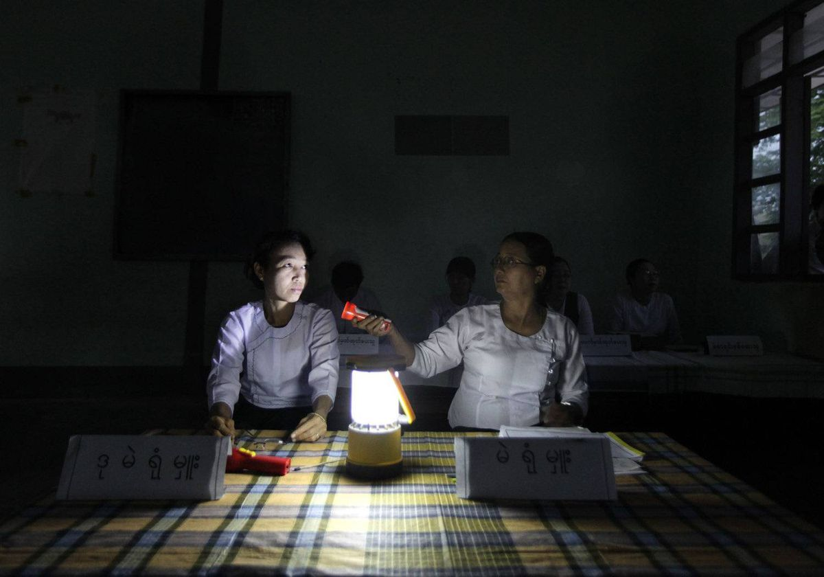 Election officials work inside a poorly lit polling station early morning before starting balloting in Wah Thin Kha, Myanmar, Sunday, April 1, 2012.