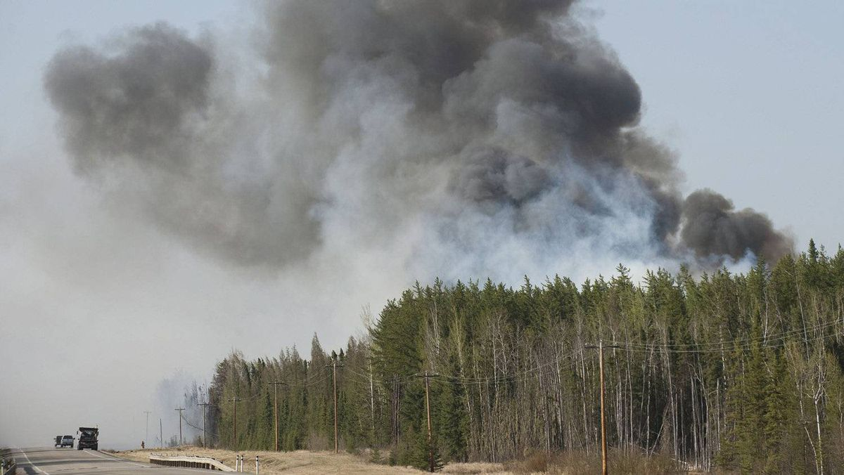 Firefighters work on a wild fire 160 km northeast of Edmonton, Alberta, on Sunday May 15, 2011. Over a thousand people were ordered to leave their homes on Sunday when strong winds fanned two separate wildfires that burned on either side of a northern Alberta town.
