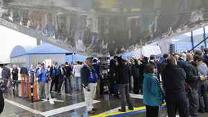 Boeing Co. workers and other guests walk under the 787 Dreamliner while it's on display at a delivery celebration in Everett, Wash.