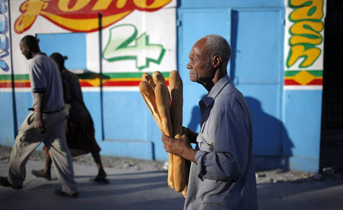 A resident walks with loaves of bread after a major earthquake hit the Haitian capital Port-au-Prince.