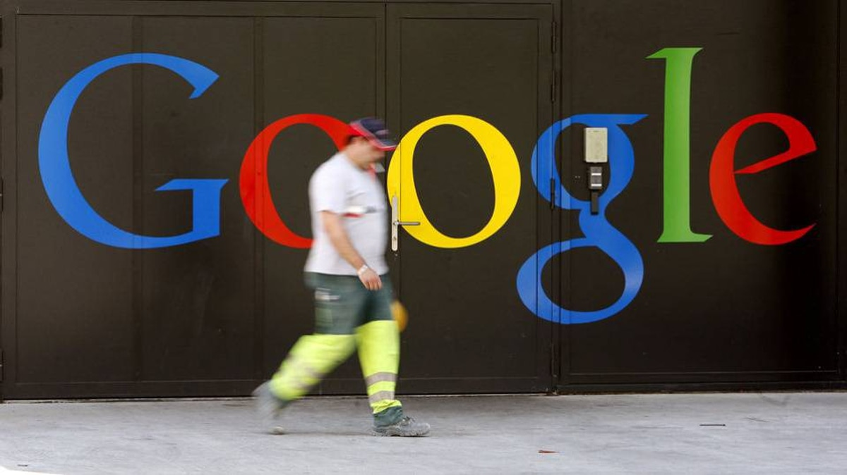 A construction worker walks past a logo next to the main entrance of the Google building in Zurich May 25, 2010.