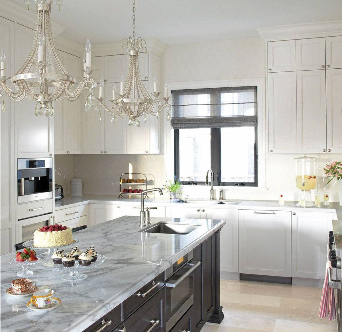 The designer created a perimeter whose layered ivory felt light and open. It started with luxurious backsplash tile, a diamond pattern of handmade ceramic by Anne Saks. Then, a matching quartz countertop and a warm white on the cabinet doors was layered on.