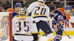 The Edmonton Oilers' Ryan Nugent-Hopkins, right, shoots past Nashville Predators goalie Pekka Rinne, during second period NHL hockey action in Edmonton, on Monday, October 17, 2011. THE CANADIAN PRESS/John Ulan