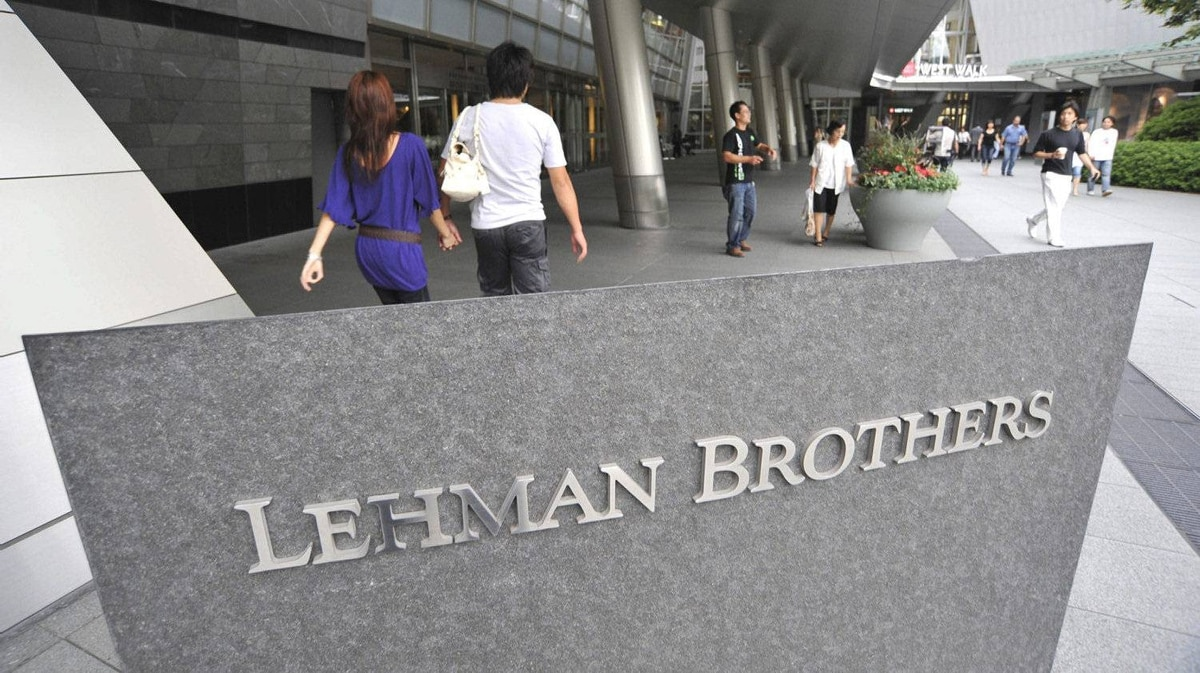 People stroll by a company sign of Lehman Brothers Holdings Inc. in front of a buiilding where its head office in Tokyo is housed Sept. 15, 2008 following the company's filing for bankruptcy protection in the United States.