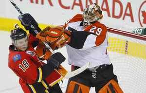 Calgary Flames forward Matt Stajanis knocked over by Philadelphia Flyers goalie Ray Emery during the third period of their NHL hockey game in Calgary, February 1, 2010.
