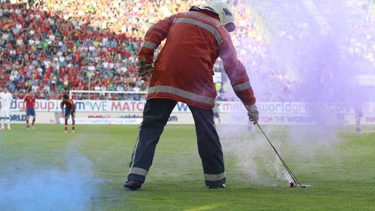 A firefighter removes a flare from the pitch during the friendly soccer match Spain against Serbia in St. Gallen May 26, 2012. REUTERS/Miro Kuzmanovic