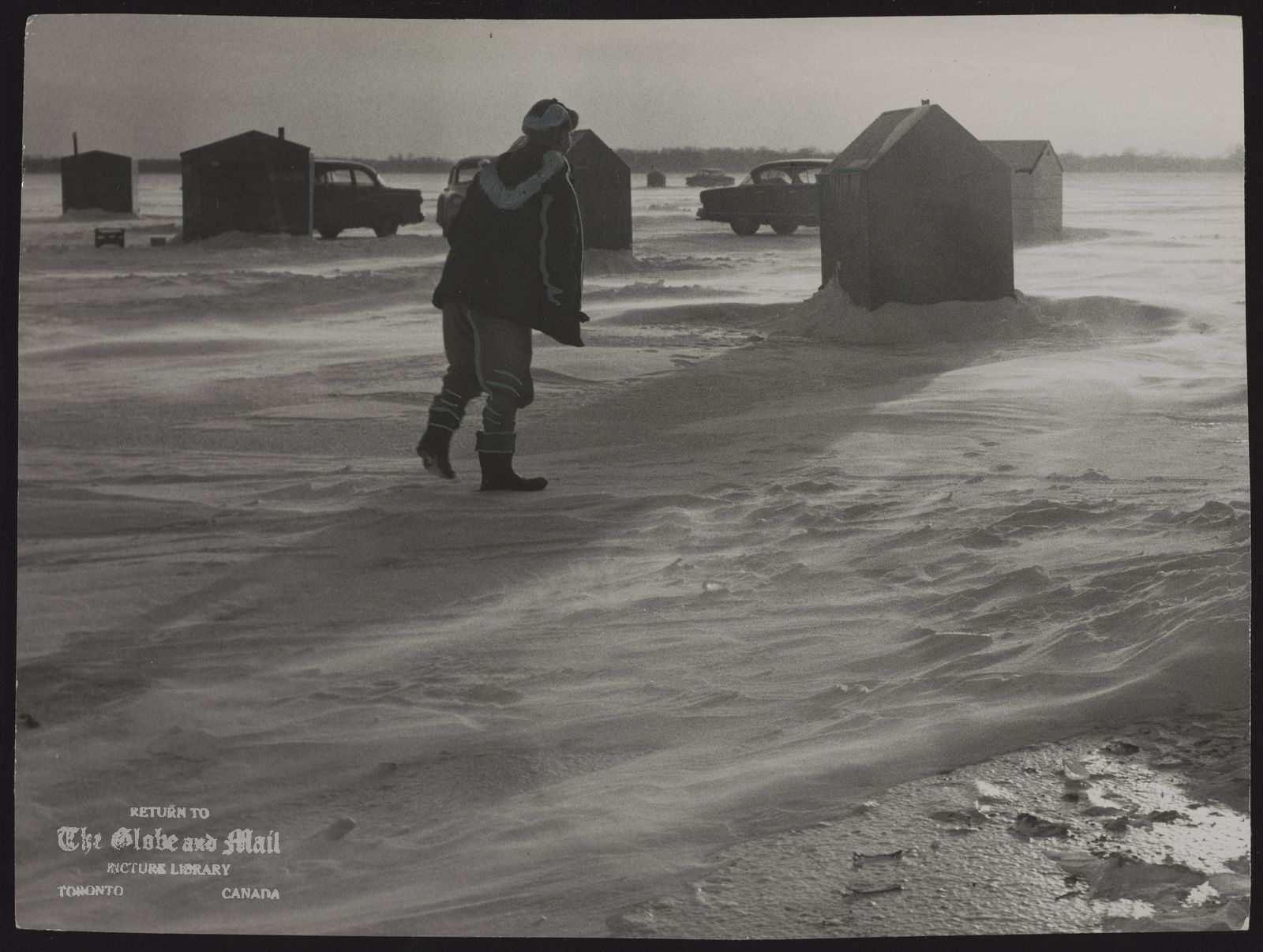 The notes transcribed from the back of this photograph are as follows: Ice Fishing Fisherman wastes no times crossing wind-swept ice from his car to oil heated cabin. It's cozy inside and fish dinner's free on lake Simcoe.