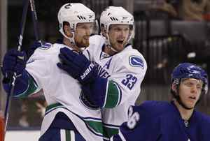 Vancouver Canucks' Daniel Sedin (L) celebrates his goal with his twin brother Henrik Sedin behind Toronto Maple Leafs' Carl Gunnarsson during the third period of their NHL hockey game in Toronto January 30, 2010. REUTERS/Mark Blinch