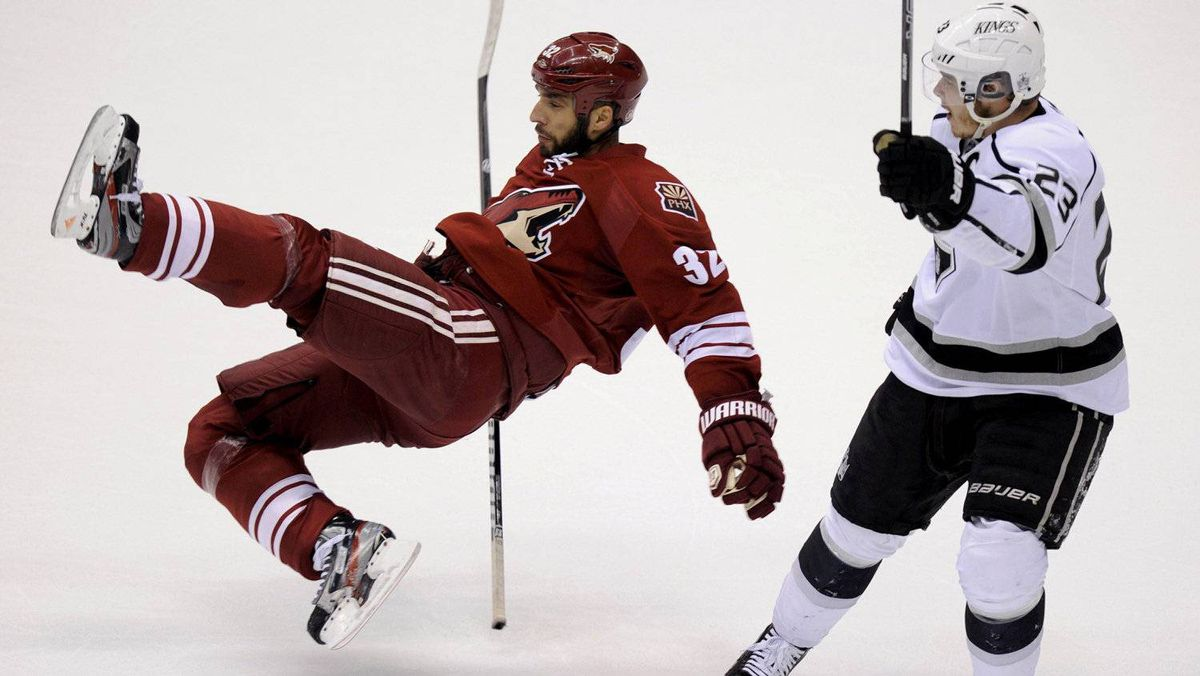 Los Angeles Kings right wing Dustin Brown (23) pick up a penalty for taking down Phoenix Coyotes defenseman Michal Rozsival (32) in the 1st period during Game 1 of the NHL Western Conference hockey finals in Glendale, Arizona, May 13, 2012. REUTERS/Todd Korol