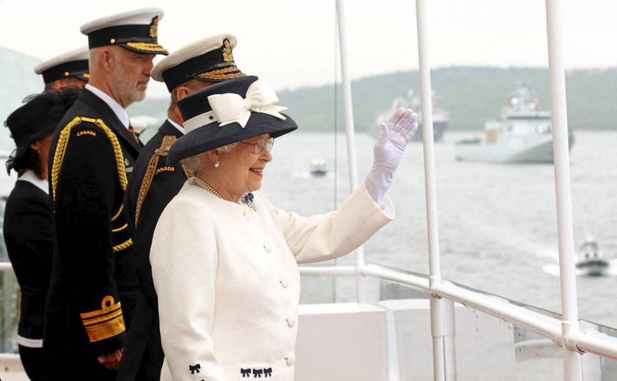 The Queen waves from the deck of the frigate HMCS St. John's as she sails past one of the 28 warships in Halifax Harbour on Tuesday.