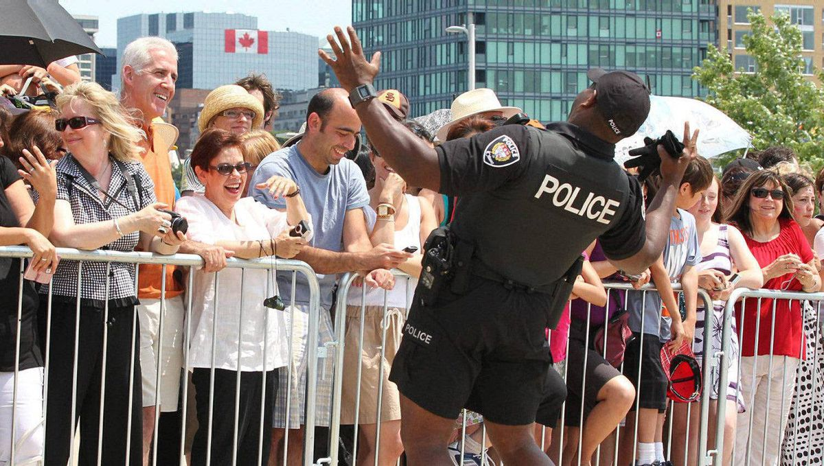Ottawa police officer Darren Joseph entertains the crowd waiting for the arrival of the Duke and Duchess of Cambridge at the War Museum in Ottawa, Saturday, July 2, 2011.