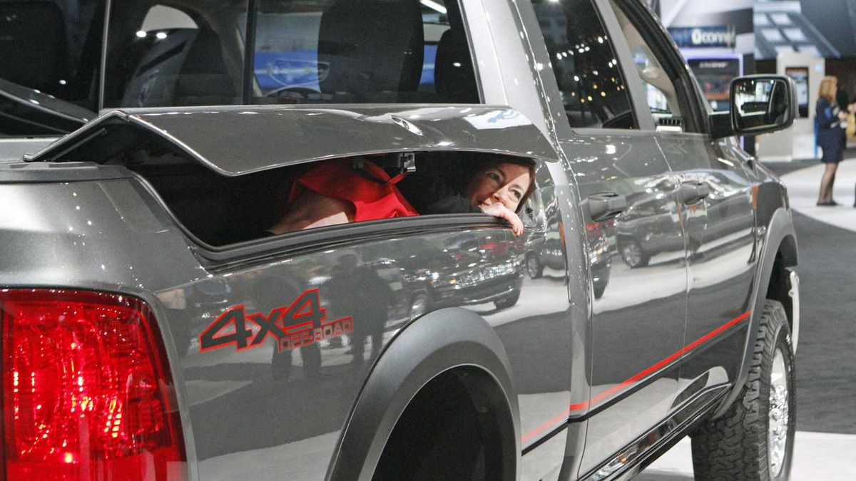 A member of the media fits into the RamBox storage area in a 2012 Dodge Ram 1500 pickup truck during the first media preview day at the 2012 Chicago Auto Show in Chicago, Illinois February 8, 2012. REUTERS/Frank Polich