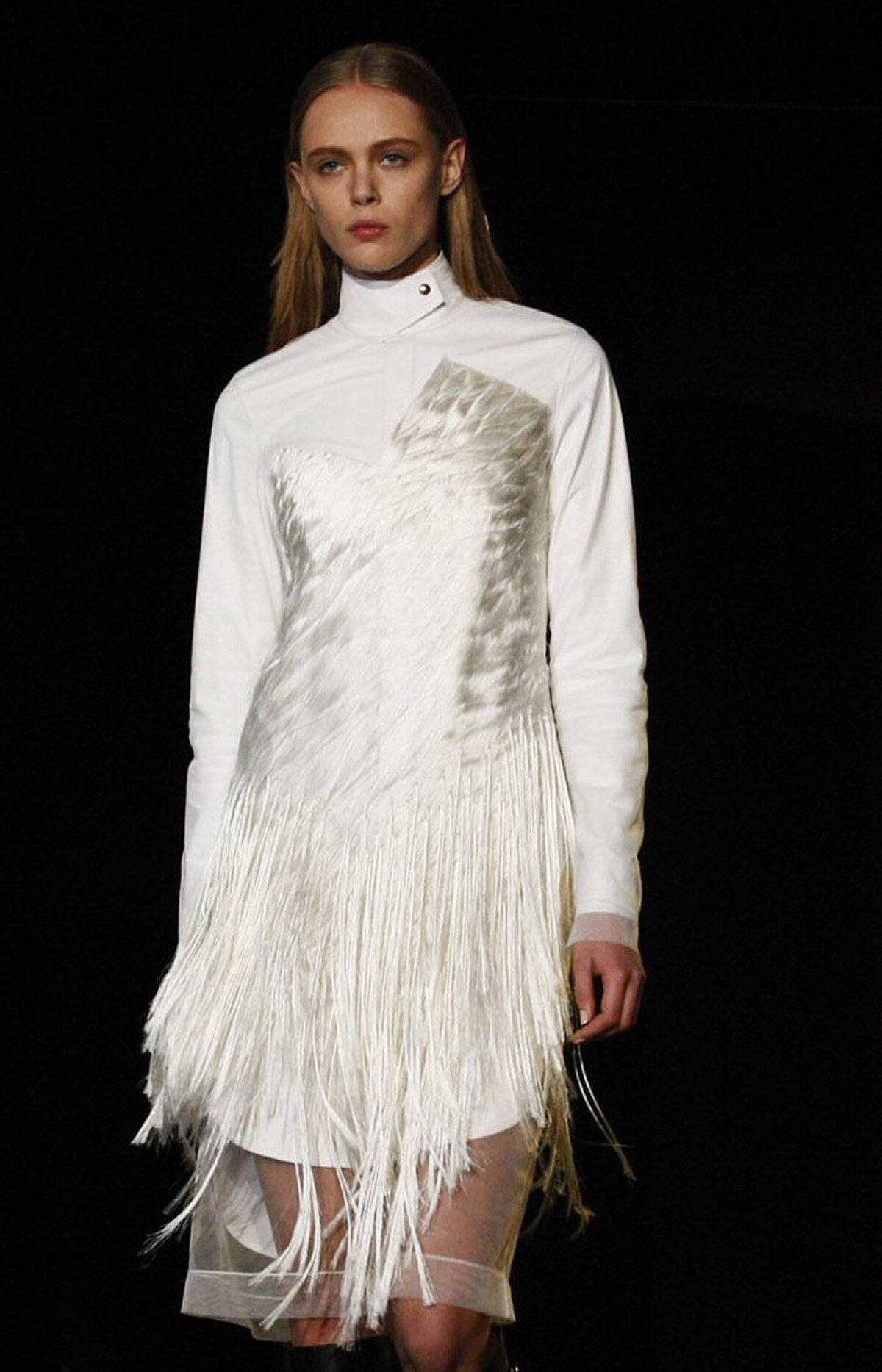 """Amid the black and oxblood, there were some winter white moments, which Wang dubbed """"peroxide."""" Here, a tulle dress with asymmetric embroidered fringe was layered overtop a shirtdress with a leather tab-collar. While few women could carry this off, it will look sharp and novel on those who do."""