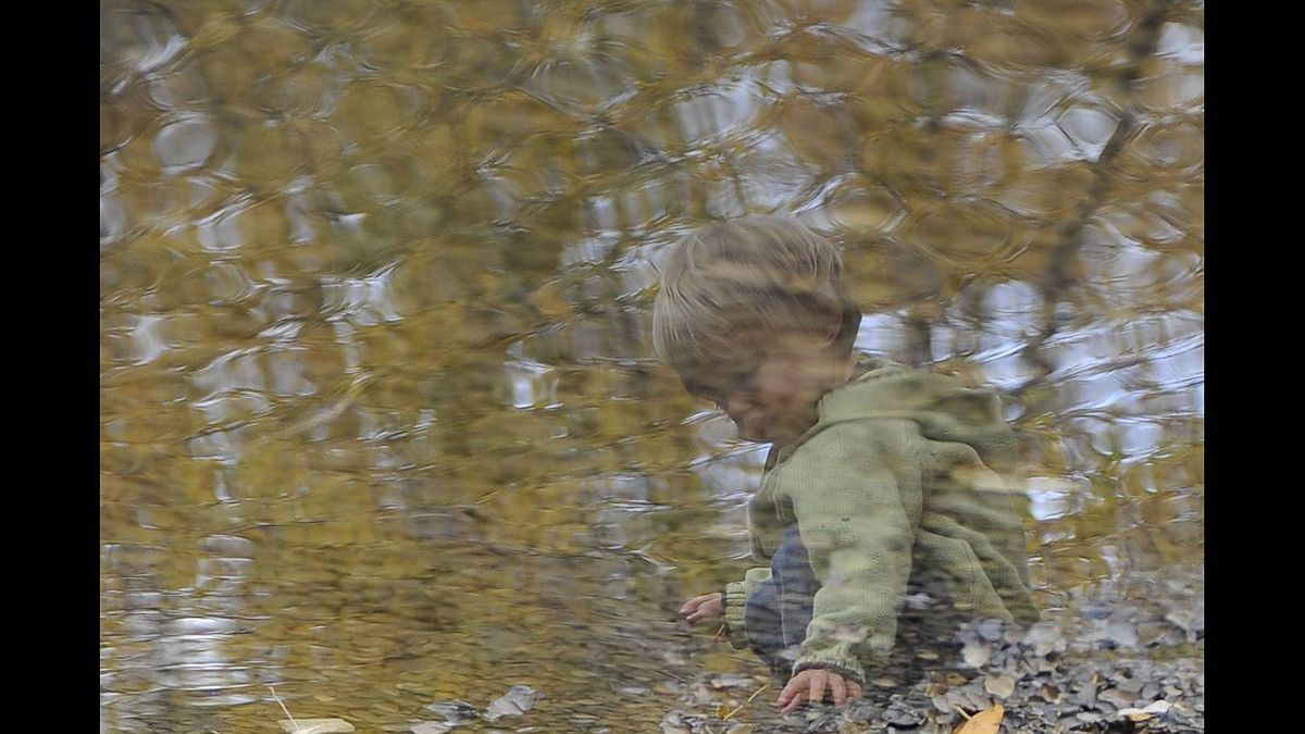 Ken Kleiner photo: Fall reflections - Every fall we capture the brief spendor of Alberta's fall with our children at a local part. This shot was snapped as our son was passing the time throwing rocks into a shallow stream at a local park.