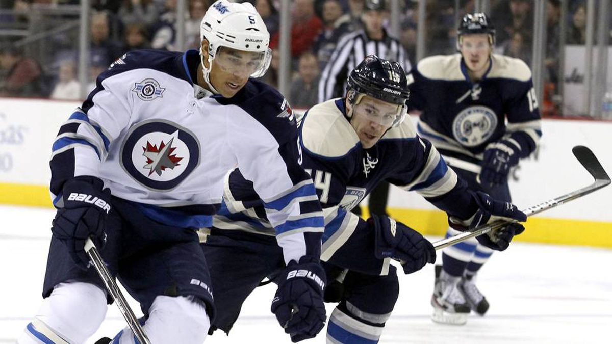 Winnipeg Jets' Evander Kane (L) fights for the puck with Columbus Blue Jackets' Grant Clitsome during the first period of their NHL hockey game in Columbus, Ohio November 12, 2011.