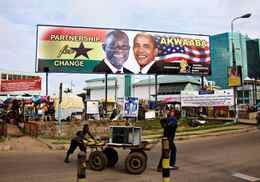 Labourers in Ghana's capital, Accra, push a cart past a billboard depicting Ghana's President John Atta Mills and United States President Barack Obama. Mr. Obama visited Ghana in July, 2009