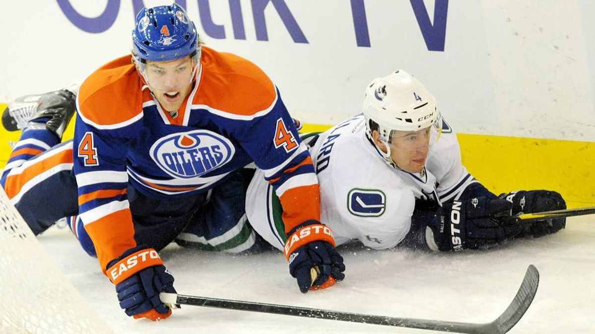 Edmonton Oilers' Taylor Hall falls on the Vancouver Canucks' Keith Ballard during first period NHL hockey action in Edmonton on Saturday.