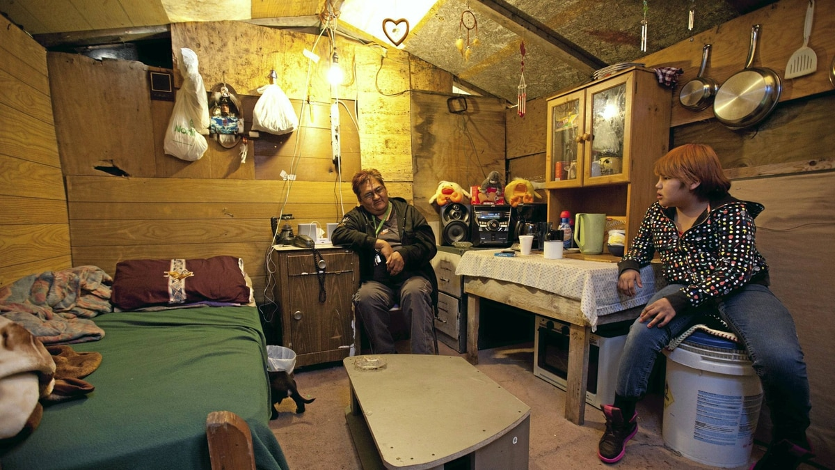 Donald Jacasum talks with Jessica Jacasum in a temporary shelter where he lives in Attawapiskat, Ont. Tuesday November 29, 2011.