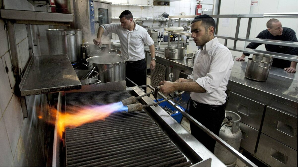 In this Thursday April 5, 2012 photo, chef Noam Dekkers , in the back, watches workers of the Tel Aviv-Jaffa rabbinate blow-torch the grill stove in one of the kitchens in Liliyot restaurant making it kosher for the Jewish holiday of Passover, in Tel Aviv, Israel.