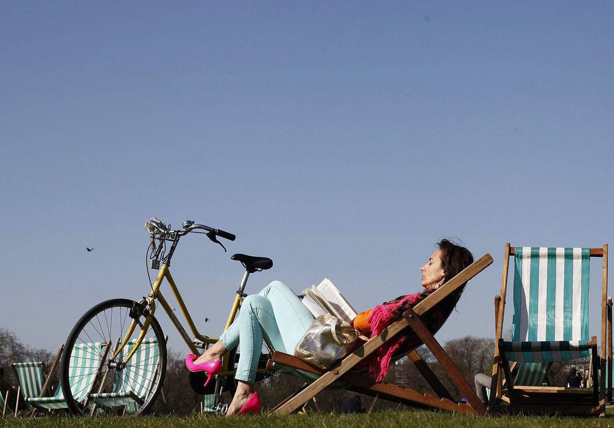 A woman enjoys the unusually warm weather as she relaxes in a deck chair in Kensington Gardens in London.