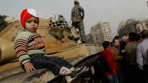 A child sits on a tank while a Egyptian soldiers stands by during a demonstration against President Hosni Mubarek in al-Tahir Square on Jan. 29, 2011 in Cairo, Egypt.