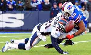 Denver Broncos cornerback Andre Goodman hits Buffalo Bills running back Tashard Choice and knocks the ball free during the second half at Ralph Wilson Stadium. Bills beat the Broncos 40-14.