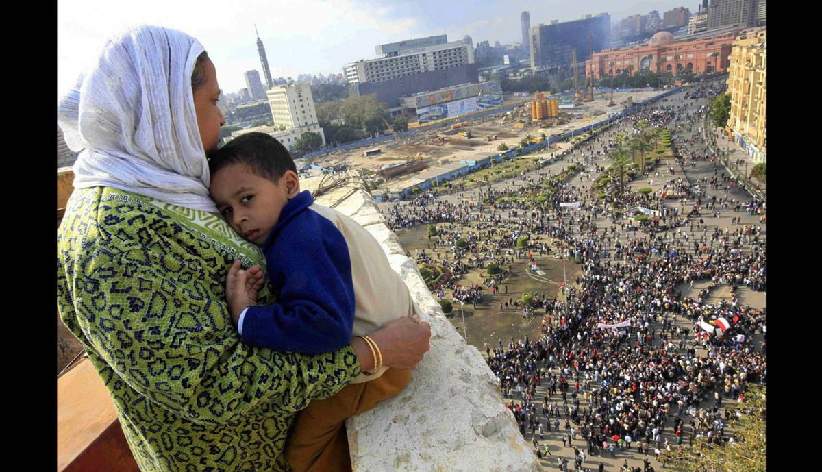An Egyptian mother hugs her child as she watches some thousands of Egyptian protesters gather at Tahrir square in Cairo, Egypt on Jan. 30, 2011.