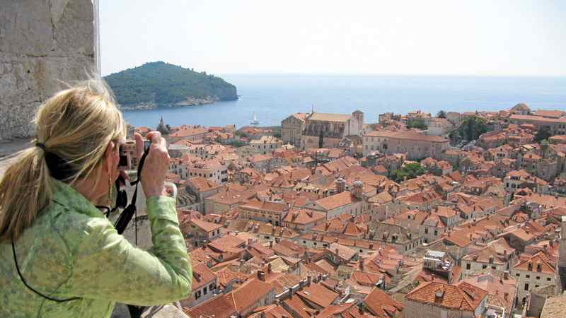 A tourist photographs the red tile roofs of Dubrovnik, Croatia. The ancient walled city is a popular stop for cruise ships in the Mediterranean
