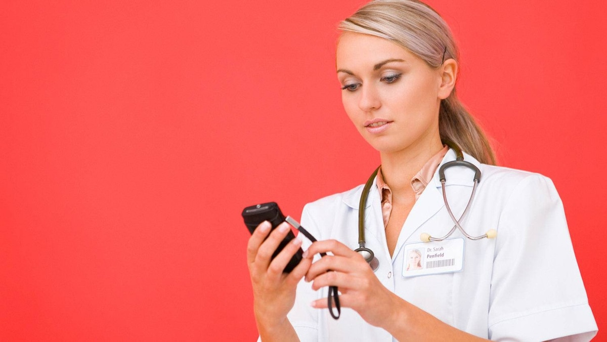 Studio shot of woman doctor with cell phone