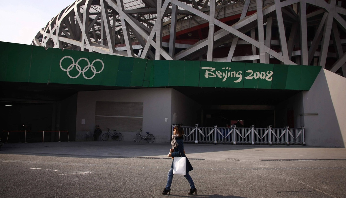 "A woman walks past a security guard outside the National Stadium, also known as the ""Bird's Nest"", which was the venue for the athletics and the opening and closing ceremonies of the 2008 Olympic Games in Beijing March 23, 2012."